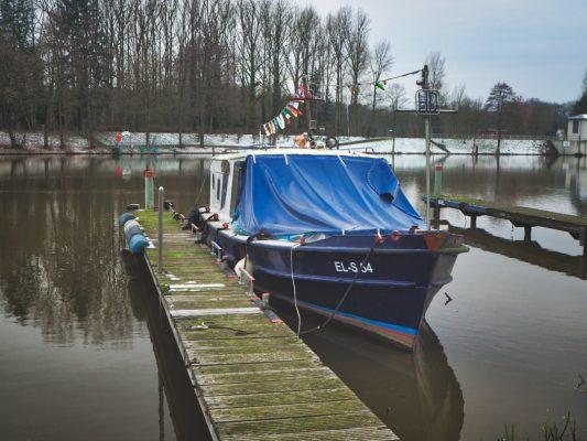 Zeigt ein Boot im Yachthafen. Es is Blau und liegt an einem schlanken verwitterten Steg.